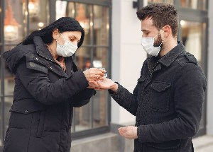 man and woman using antiseptic