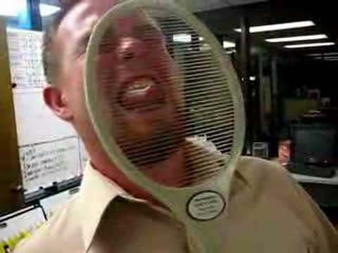 man touching electric fly swatter with his tongue