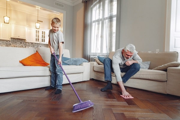 man and child cleaning the floor