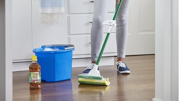 woman cleaning floor with pine sol